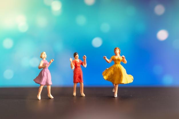 Woman in colored dress dancing against bokeh background Premium Photo
