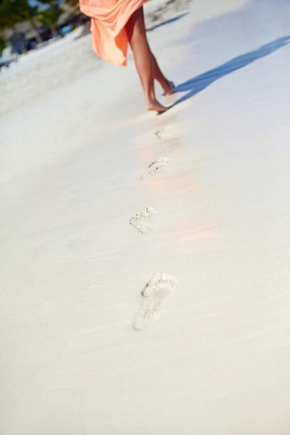 Woman in colorful dress walking on beach ocean leaving footprints in the sand Free Photo