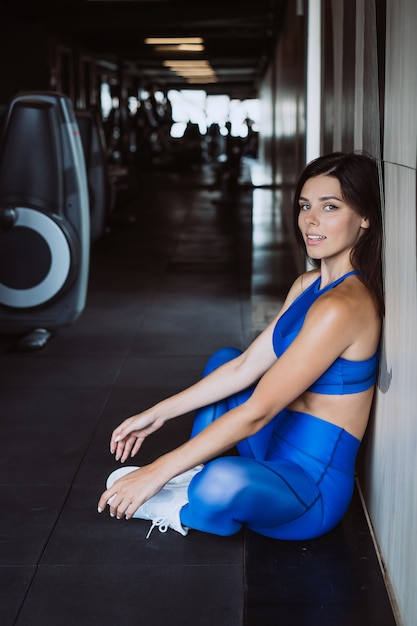 Woman in comfortable sports resting leaned against wall, finished workout girl gather energy concept Free Photo