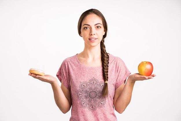 Woman comparison doughnut and apple Free Photo