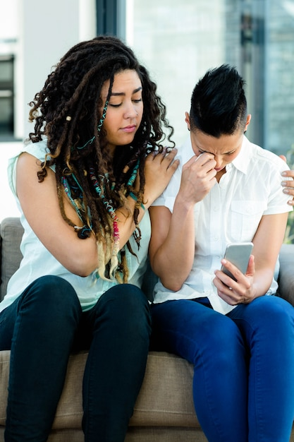 Woman consoling her partner after reading a message in living room Premium Photo