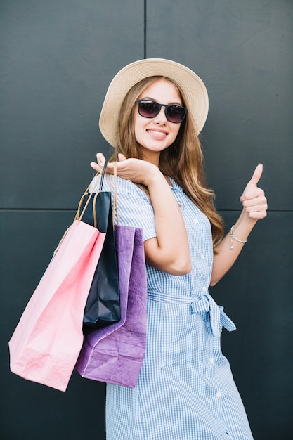 Woman content with purchases posing at camera Free Photo