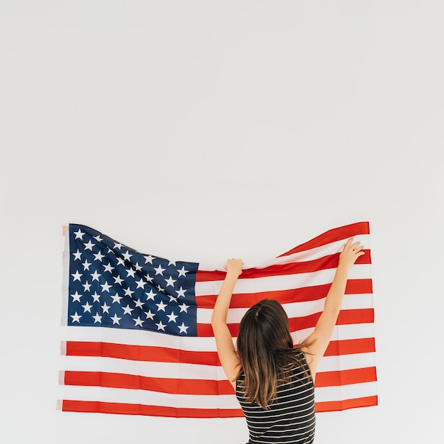 Woman correcting flag of america on wall Free Photo