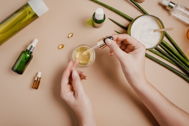 Woman cosmetologist cosmetics testing. natural organic cosmetics. serum hair mask. flat lay pastel Premium Photo