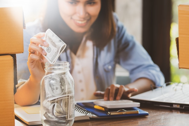Woman counting and putting money banknotes into the glass bottle for saving money. Premium Photo