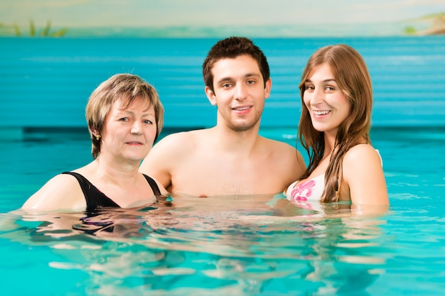 Woman and couple in swimming pool Premium Photo