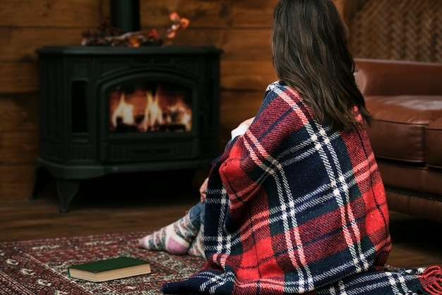Woman covered in blanket next to fireplace Free Photo