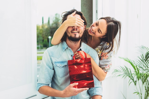 Woman covering eyes of man with gift bag Free Photo