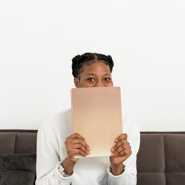 本で顔を覆っている女性 無料写真