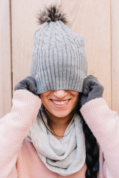Woman covering face with cap Free Photo