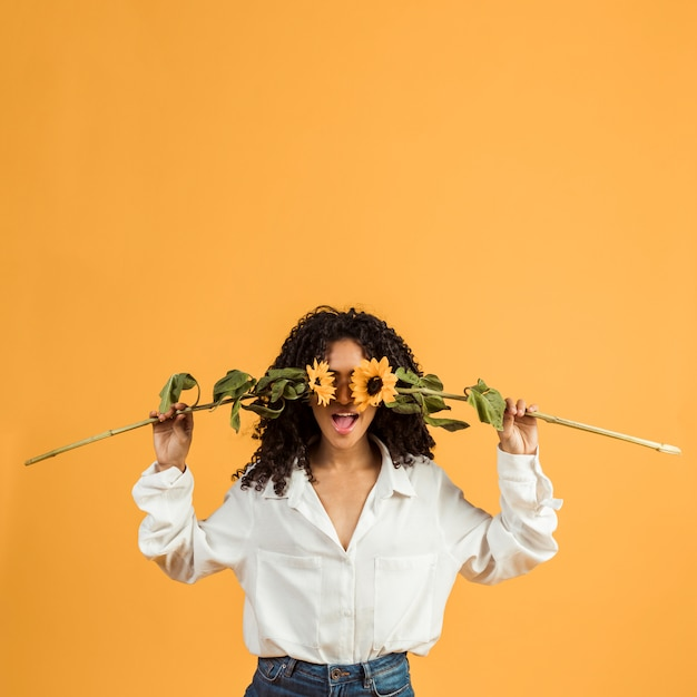 Woman covering face with flowers Free Photo
