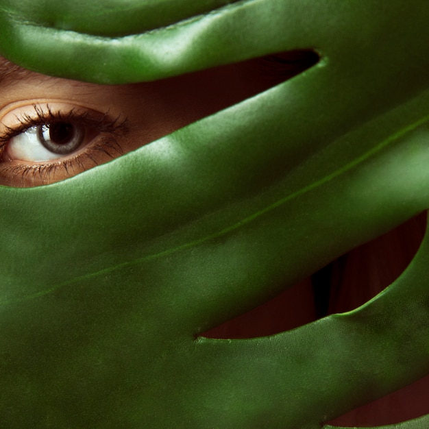 Woman covering face with green leaf Free Photo