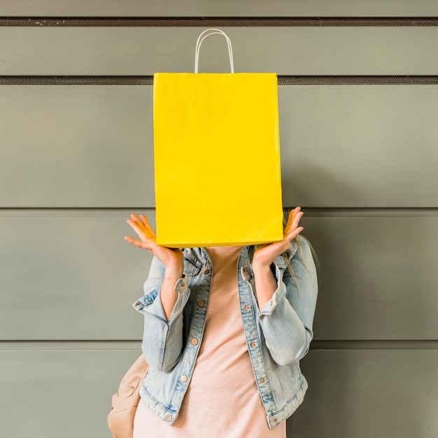 Woman covering face with yellow shopping bag Free Photo