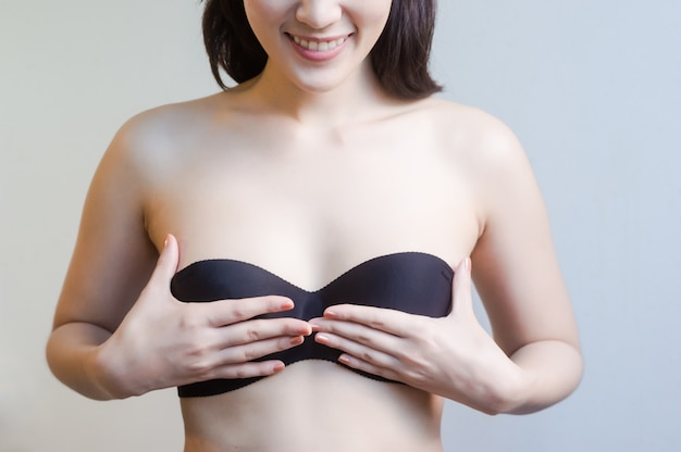 Woman covering her breast with hands while standing isolated on background Premium Photo