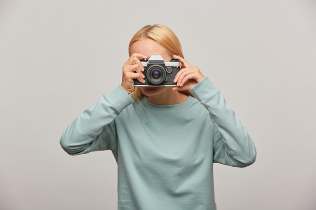 Woman covering her face with the camera making a photo session Free Photo