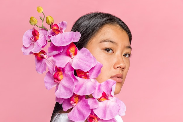 Woman covering her face with orchid and looking at camera Free Photo