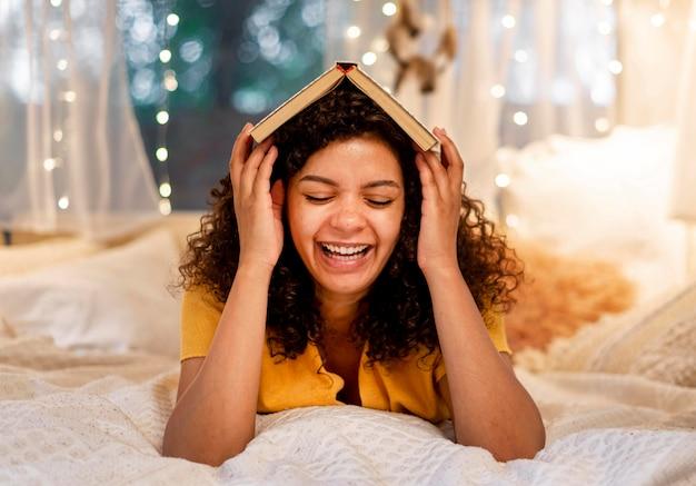 Donna che copre la testa con vista frontale del libro Foto Gratuite