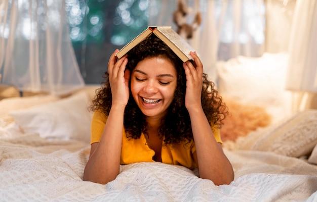 Donna che copre la testa con il libro Foto Gratuite