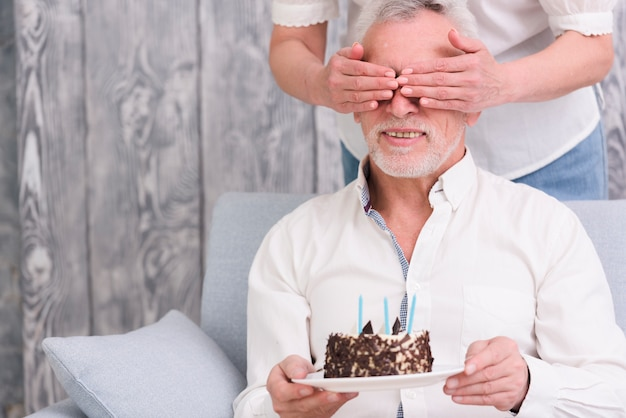 Woman covering her husband's eyes holding birthday cake in hand Free Photo