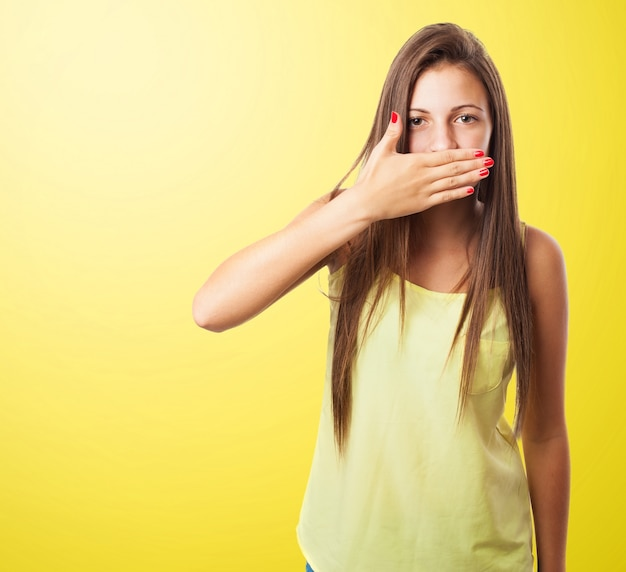 Woman covering her mouth in a yellow background Free Photo
