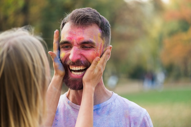 Woman covering a man's face with paint Free Photo
