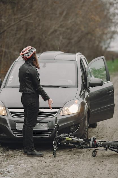 La donna si è schiantata contro la macchina. ragazza in un casco. le persone litigano per l'incidente. Foto Gratuite