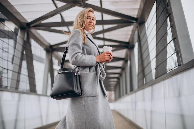 Женщина пересекает мост и пьет кофе Бесплатные Фотографии