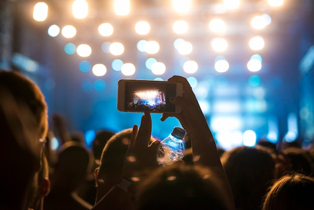 Woman in the crowd taking picture of stage at music festival Free Photo