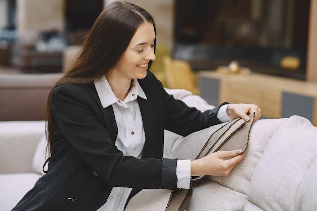 Cliente della donna che cerca bello tessuto nel negozio dei drappi Foto Gratuite