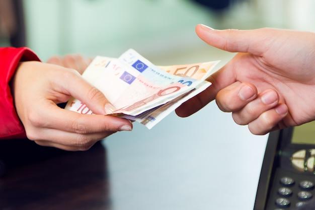 女性顧客はお金でお金を払っています。手の詳細。 Premium写真
