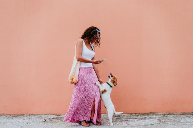 フルーツが付いている綿袋を持って、街を歩いている女性かわいい犬の女性。 Premium写真