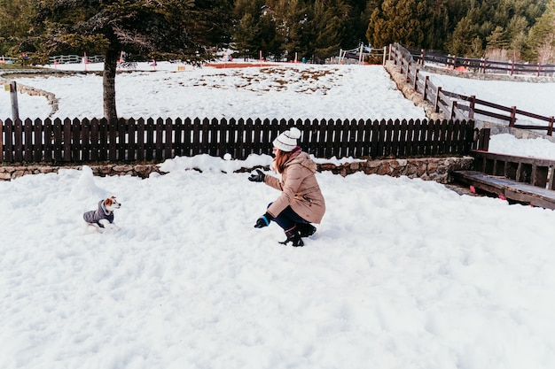 Woman and cute jack russell dog enjoying outdoors at the mountain with snow. Premium Photo