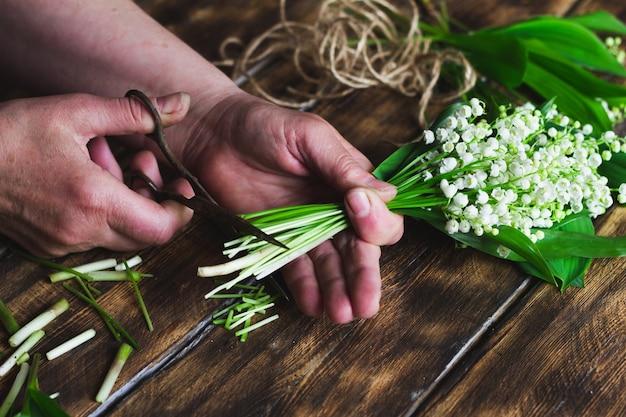女性はスズランの花束を切ります。 Premium写真