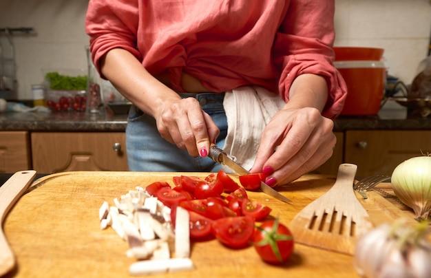 Woman cutting cherry tomatoes and mushrooms Premium Photo