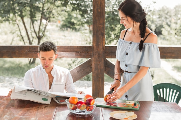 Woman cutting fruits looking at her husband reading newspaper Free Photo