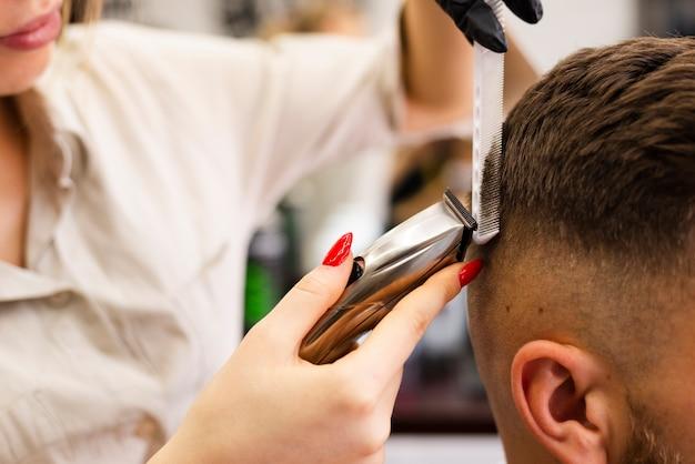 Woman cutting a man's hair close-up Free Photo