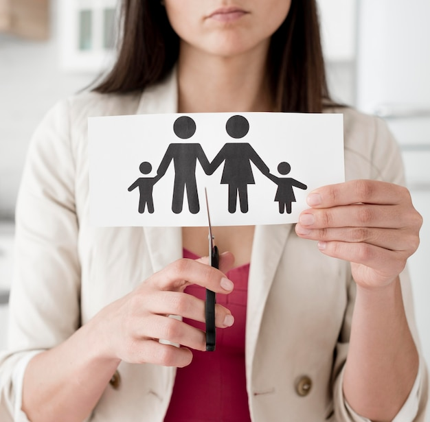 Woman cutting paper family with scissors Free Photo