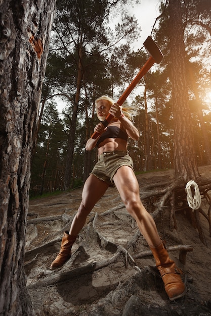Woman cutting with an ax in high Free Photo