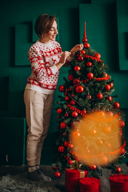 Woman decorating christmas tree with red balls Free Photo