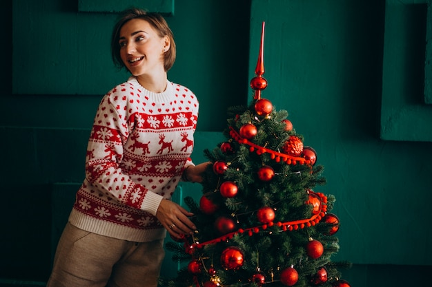 Woman decorating christmas tree with red toys Free Photo