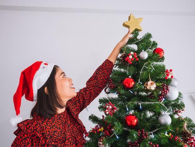Woman decorating christmas tree with stars Premium Photo