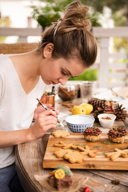 Woman decorating gingerbread with brush Free Photo