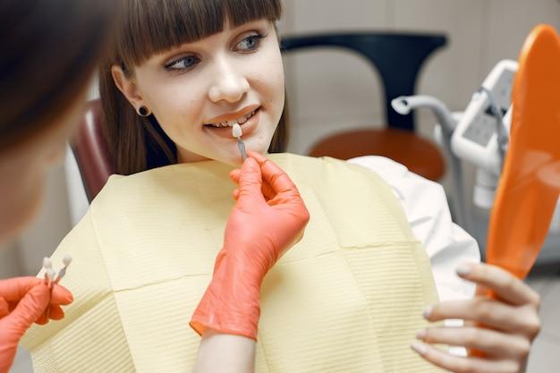 Donna su una poltrona odontoiatrica. la ragazza sceglie un impianto. la bellezza tratta i suoi denti Foto Gratuite