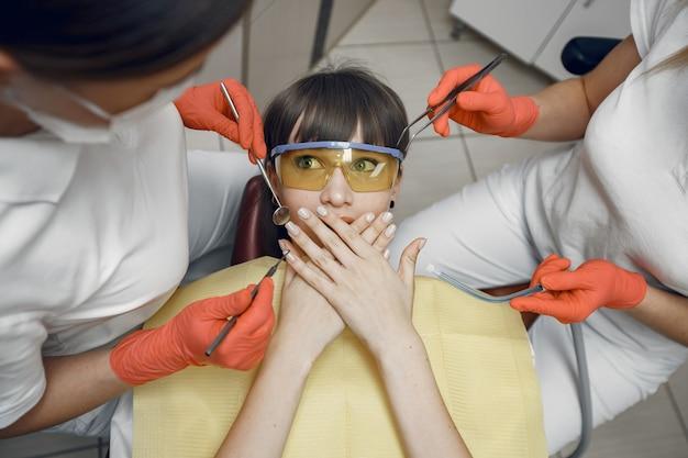 Donna su una poltrona odontoiatrica. la ragazza si copre la bocca i dentisti trattano i denti di una ragazza Foto Gratuite