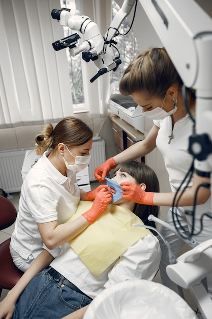 Woman in a dental chair. girl is examined by a dentist.dentists treat a girl's teeth Free Photo