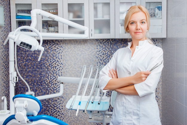A woman dentist in white uniform poses against a of dental equipment in a dental office Premium Photo