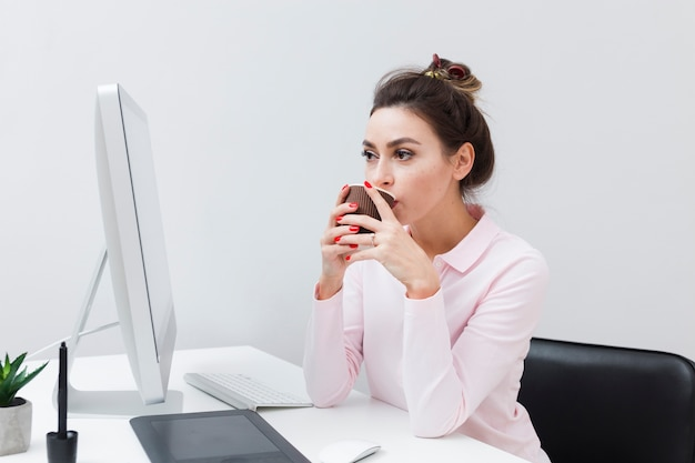 Woman at desk drinking coffee and looking at computer Free Photo