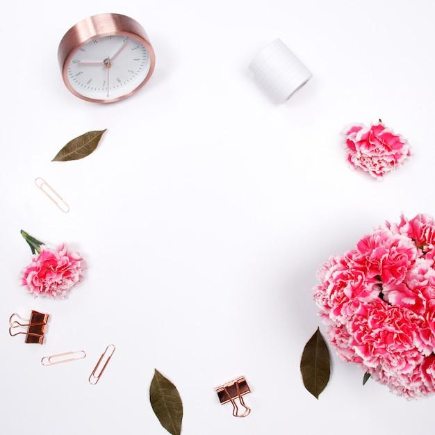 白い背景にピンクのカーネーションの花と女性のデスクワークスペースのフレーム。 Premium写真