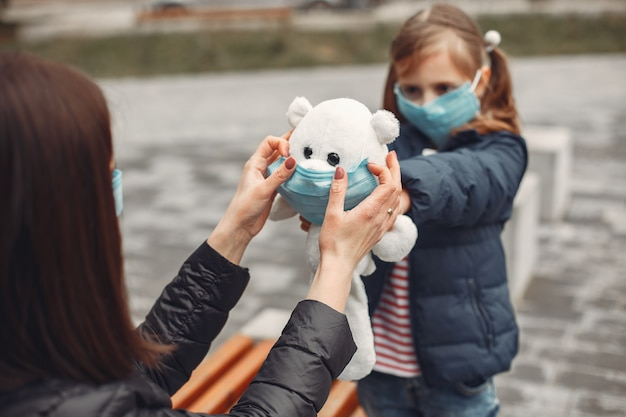 Woman in a disposable mask is teaching her child to wear a respirator Free Photo