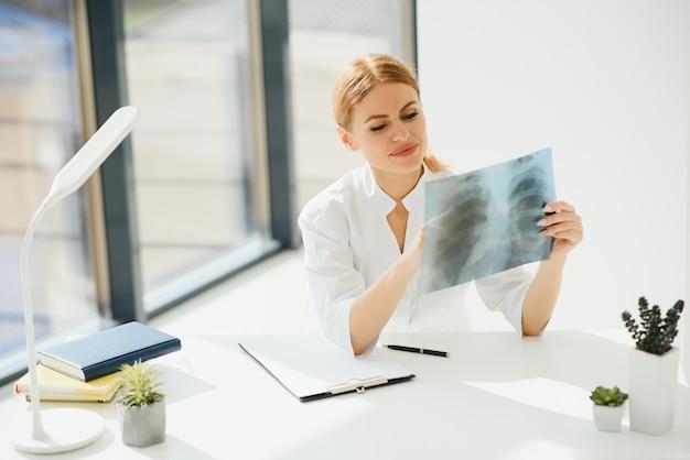 Женщина-врач руки держит рентгеновский снимок грудной клетки пациента перед лечением Premium Фотографии